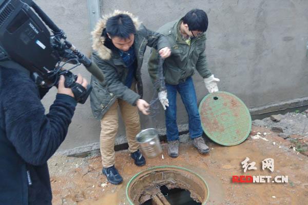 执法工作人提取企业污水样本。